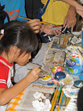 Girl painting art. Young Asian girl painting with water colours with other children Stock Images
