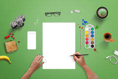 Girl painting on a blank white paper with brush and water colors. Top view of green desk Royalty Free Stock Photo
