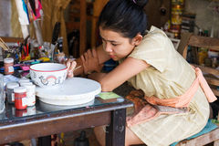 The girl is painting the bowl Stock Photos