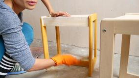A girl is painting a chair. Repair in the apartment with your own hands. stock video footage