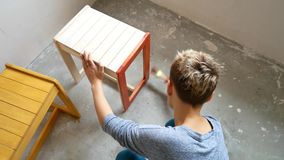 A girl is painting a chair. Repair in the apartment with your own hands. stock video