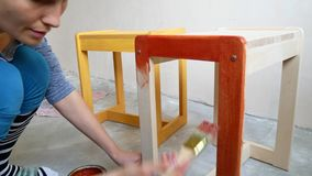 A girl is painting a chair. Repair in the apartment with your own hands. stock footage