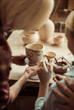 Girl painting clay pot and grandparents helping at workshop Royalty Free Stock Photos