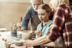 Girl painting clay pot and grandparents helping at workshop. Side view of girl painting clay pot and grandparents helping at workshop stock images