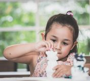 Girl painting a doll in Art classroom. Girl is painting a doll in Art classroom royalty free stock photography