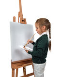 Girl painting on easel Stock Images