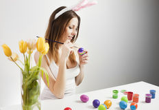 Girl painting easter eggs. Pretty brunette painting colorful easter eggs in spring Stock Image