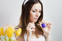 Girl painting easter eggs. Pretty brunette painting colorful easter eggs in spring Royalty Free Stock Photos