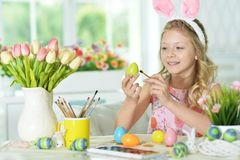 Girl  painting eggs. Little girl painting eggs for Easter holiday Stock Image