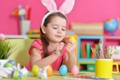 Girl  painting eggs. Little girl painting eggs for Easter holiday Stock Photos