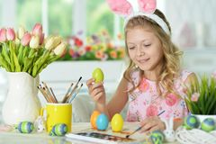 Girl  painting eggs. Little girl painting eggs for Easter holiday Royalty Free Stock Images