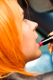 Girl painting her lips doing make up while driving the car. Stock Photo