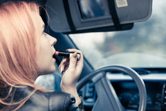 Girl Painting Her Lips Doing Make Up While Driving The Car. Royalty Free Stock Photography