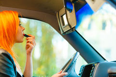 Girl Painting Her Lips Doing Makeup While Driving The Car. Stock Images
