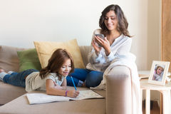 Girl painting with her mom chating. Little girl painting in the living room while mom is on internet Royalty Free Stock Images