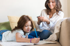 Girl painting with her mom chating. Little girl painting in the living room while mom is on internet Stock Photography