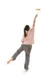 Girl painting high with roller. Young woman reaching high to paint with a roller. Back view Royalty Free Stock Images