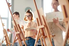 Girl at painting lesson. One of students of painting school looking at camera while standing in front of easel with palette and paintbrush royalty free stock photo