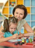 Girl painting with mother Stock Photos