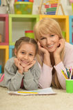 Girl painting with mother Stock Images