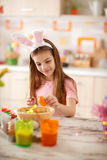 Girl painting orange egg with watercolor Royalty Free Stock Photo