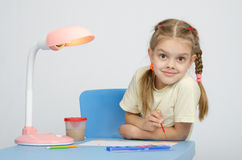 Girl painting paints at the table, looked into frame Royalty Free Stock Photo