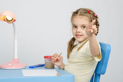 Girl painting paints at table, points the finger Stock Photos