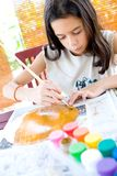 Girl painting a paper plate with poster paint Stock Photography