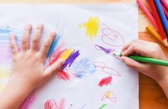 Girl painting on paper sheet with colour pencils on the wooden table at home - child kid doing drawing picture and colorful crayon stock photo