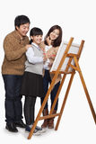 Girl painting with parents, studio shot Royalty Free Stock Images