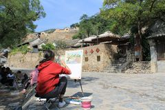 Cuandixia village on a painting. Girl painting a picture of the ancient village Cuandixia. She is sitting in front of the old buildings, wearing red sweatshirt royalty free stock photography