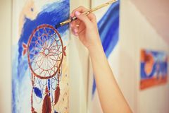 Girl painting a picture in home studio. Model woman painting her picture. Art. Woman draws paints. Girl engaged in creativity. Mod. El painting brush on easel Stock Photos