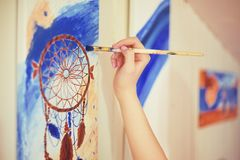 Girl painting a picture in home studio. Model woman painting her picture. Art. Woman draws paints. Girl engaged in creativity. Mod. El painting brush on easel Stock Photo