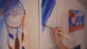 Girl painting a picture in home studio. Model woman painting her picture. Art. Woman draws paints. Girl engaged in creativity. Mod stock video
