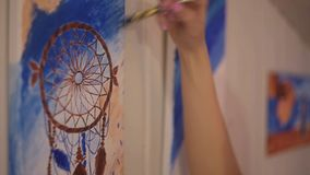 Girl painting a picture in home studio. Model woman painting her picture. Art. Woman draws paints Dreamcatcher. stock footage