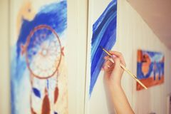 Girl painting a picture in home studio. Model woman painting her picture. Art. Woman draws paints. Girl engaged in creativity. Mod. El painting brush on easel Royalty Free Stock Photography