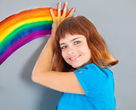 A girl is painting a rainbow on the wall Royalty Free Stock Photos