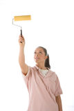 Girl painting with roller. Young woman painting with a roller. Frontal view Royalty Free Stock Photos