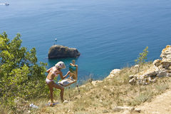 Girl painting sea. FIOLENT, CRIMEA, UKRAINE - JULY 24, 2010: girl painting seascape, recorded in village Fiolent in region Crimea on Black sea, Ukraine. Fiolent royalty free stock photo