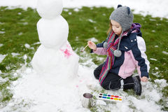 A girl painting a snowman Royalty Free Stock Images