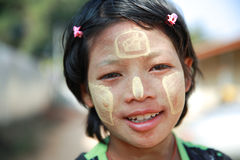 Girl painting tanaka on face. MAE SOT THAILAND - JAN3 : Unidentified girl descendant migrant worker use of Thanaka, a traditional Myanmar cosmetic painting on Royalty Free Stock Photos