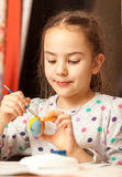 Girl painting traditional easter eggs at home Stock Images