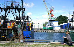 Girl painting trawler equipement fishing boat. Girl painting trawler equipment fishing boat harbor Stock Photography