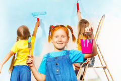 Girl painting wall with friends. Little girl in blue holds pail and brush smiling, while her friends paint the wall on a background Stock Photos