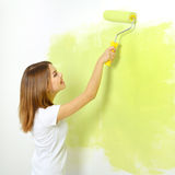 Girl painting a wall Stock Images