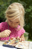 A girl painting with water colors (watercolors), painting a paper plate. With watercolor paints outside in garden Stock Photography