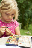 A girl painting with water colors (watercolors), painting a paper plate. With watercolor paints outside in garden Stock Photos