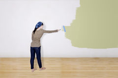 Girl painting on white wall Stock Photo
