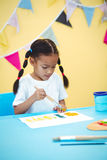 Girl painting with yellow and green colours Stock Photo
