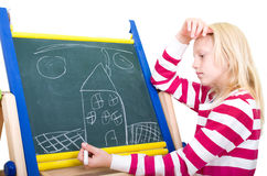Girl paints on the chalkboard Stock Photography